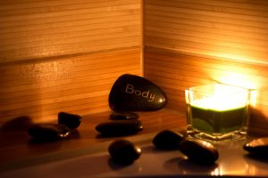 black lava stones massage and a green candle